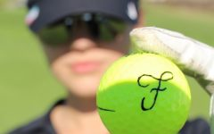 Fabi Sanchez holding up a golf ball with her first initial written on it.