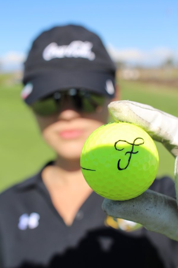 Fabi+Sanchez+holding+up+a+golf+ball+with+her+first+initial+written+on+it.