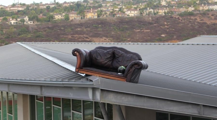 A black, leather sofa sits perched on top of the roof of the Bobcat arena.