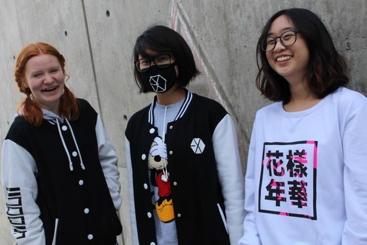 Pheobe Tran, Heidi Gertzki, and Varintorn Nivasnandas pose with some kpop shirts