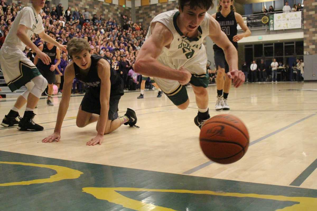Senior forward Bryce Buscher dives for a loose ball late in the fourth quarter against CHS.