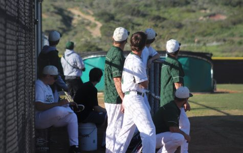 Sage Creek's dugout looks off into the distance as the ball flies and the runs score.