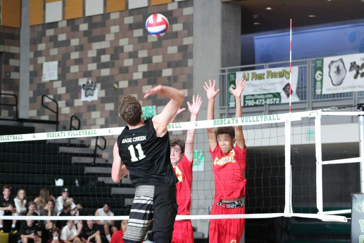 Junior Christian Janke soars above the net in preparation for a kill.