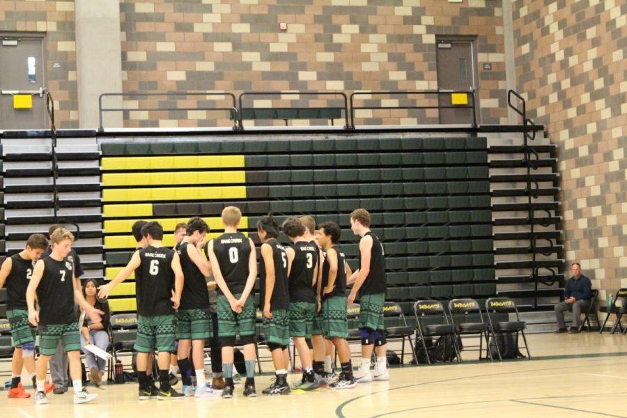 During a timeout, the varsity team huddles around to strategize for the rest of the fourth set.