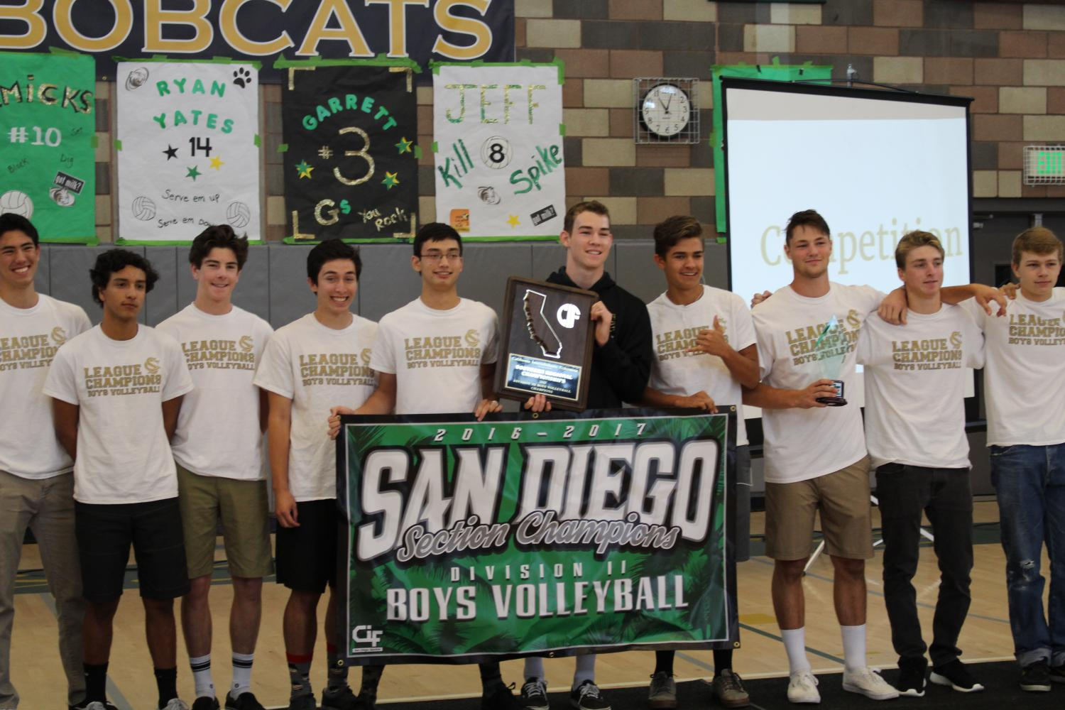 Boys Varsity Volleyball team stands united with their State Championship banner.