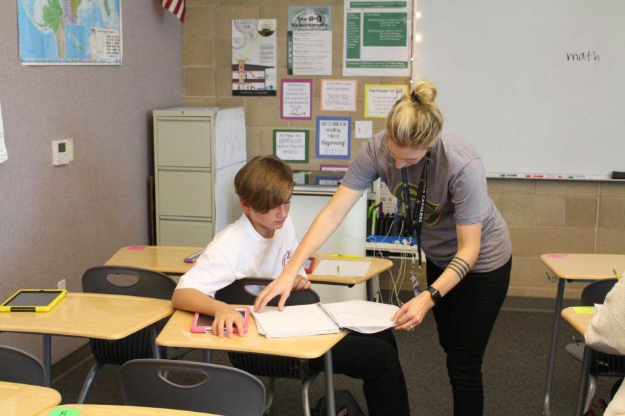 McLean aids student, Luke Beifus, in math class.