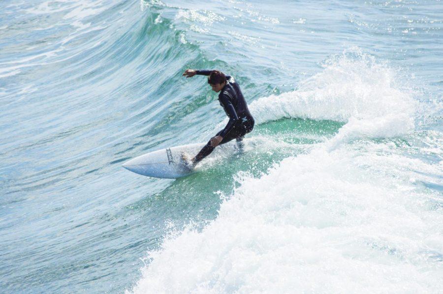 Senior David Fosman surfs the south side break of the Oceanside pier.