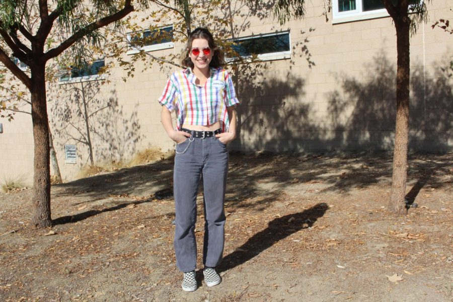 Junior Skylar Johnson rocks a retro colorful button down that she ties with baggy faded blue jeans. She adds accessories like a big black belt, checkered Vans, red old school glasses and a silver chain. She gets the majority of her clothes from other vendors when they swap back and forth on Depop. Check out her shop on Depop! https://www.depop.com/scaryskylar