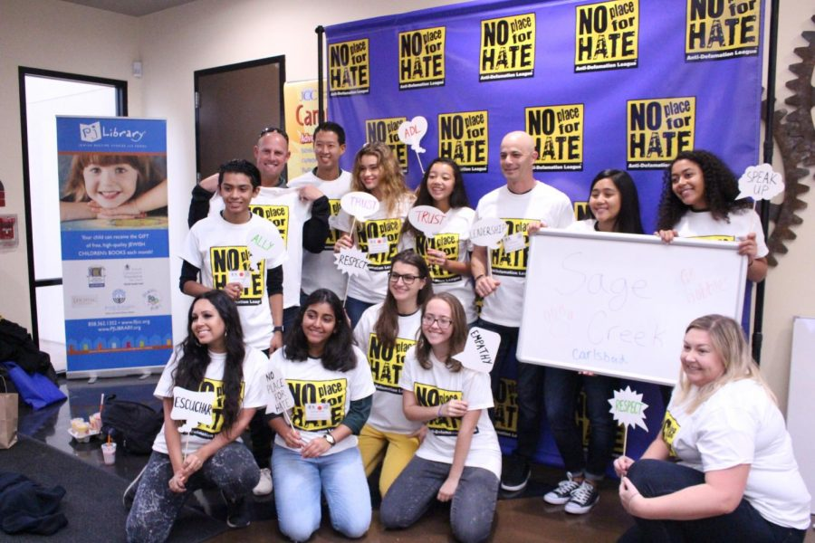 No Place for Hate team lines up for a photo in their new shirts while holding up words of kindness.