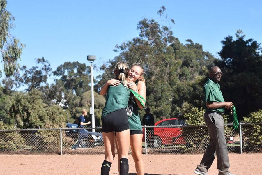 Brooklynn Deal (junior) embraces teammate, Natalie Huestis (sophomore) once receiving her 1st place team medal after racing 19:45 at the San Diego CIF Cross Country Championships. After three long seasons of racing Cross Country, this accomplishment had overjoyed Deal with all of the hard work that she had devoted to the sport throughout her high school career.