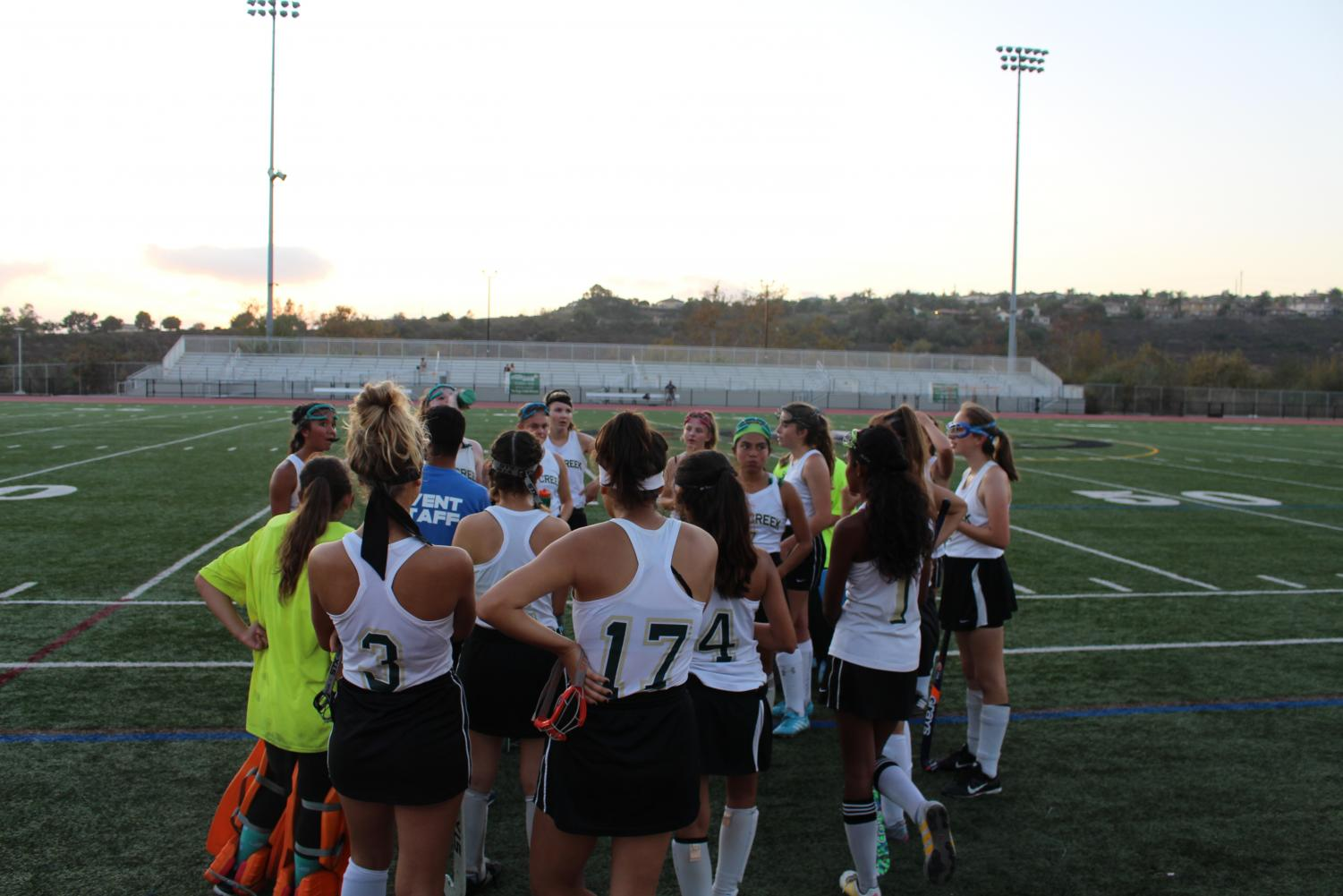 Girls field hockey team huddles up before a game.