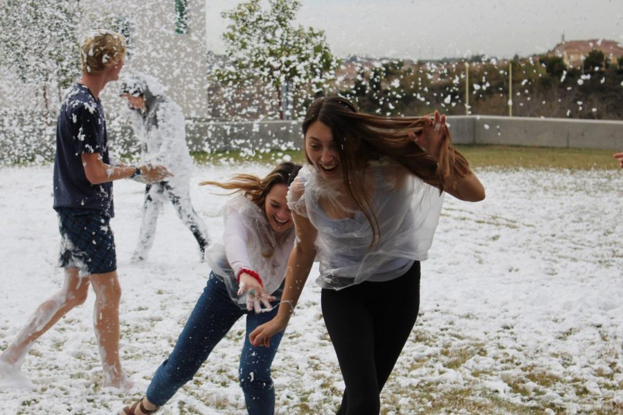 Seniors Paige Loeffler and Makenna Manti are seen running, as well as slipping, through Dr. Bronner's snow on the Wednesday of Hoopcoming week.