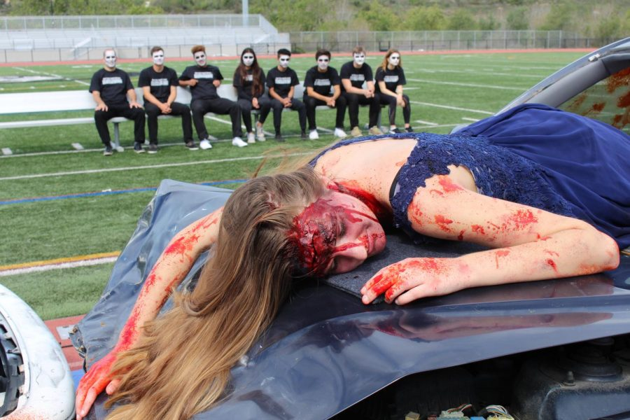 Summer Fitzgerald, a junior at Sage Creek, is displayed laying on the hood of a crashed vehicle for the Every 15 Minutes scene, put on by nine of our very own students.