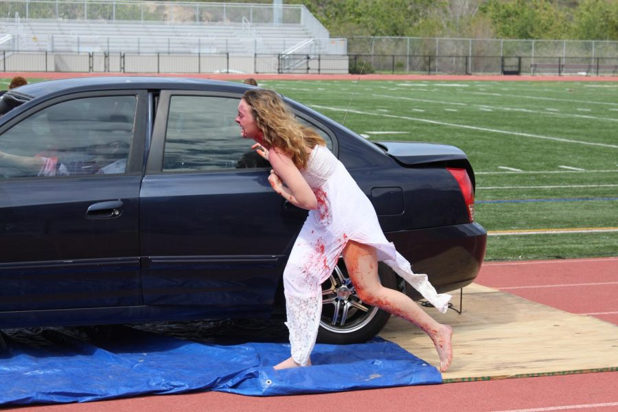 Senior Paige Loeffler rushes out of the vehicle to evaluate the extent of the injuries caused during the Every 15 Minutes simulation.