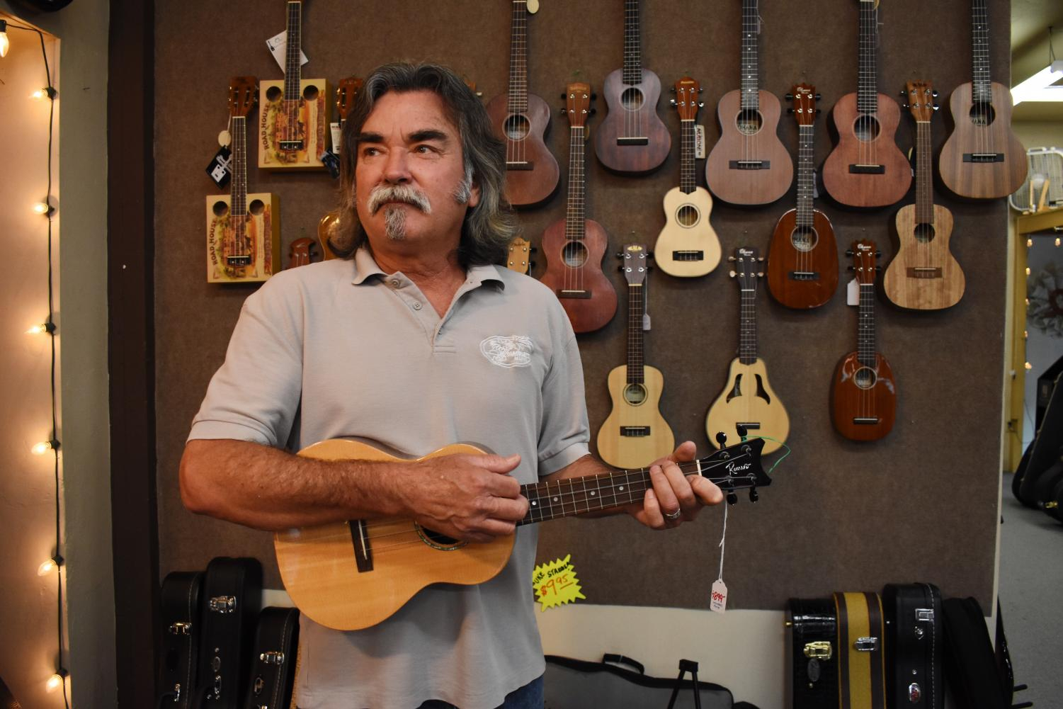 Roy Good plays ukulele inside the shop he has been working at for over three decades.