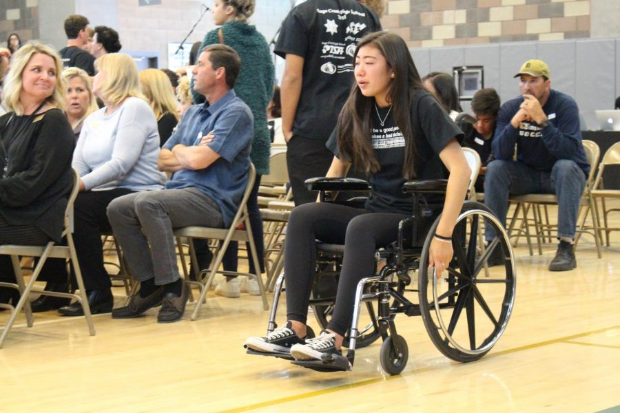 Senior Bailee Brennan, recently paralyzed in the accident, returns to her seat after speaking with tears streaming down her face.