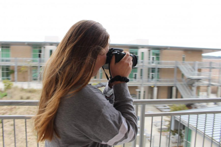 Sierra Jorden aims her camera at Sage Creek's architecture. She has been in yearbook for three years where she focuses on documenting the students of Sage Creek.