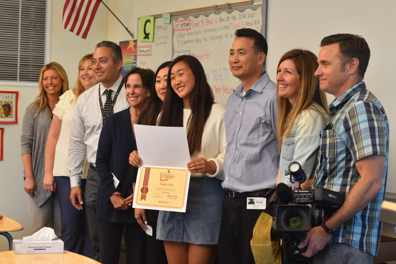 "Senior Emily Sim, stands proudly with her newly accumulated certificate, next to her parents and school staff. She was interviewed on her successes with her ""Senior Prom"" Genius project for NBC 7 News broadcasters."