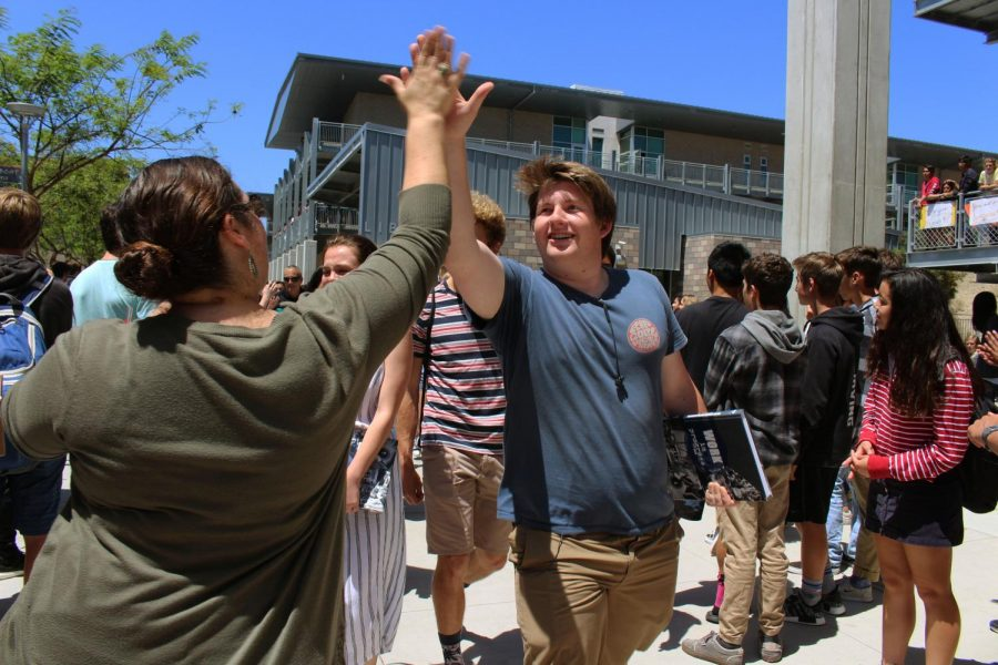 Senior Christian Davis high fives a faculty member while departing Sage Creek towards the conclusion of the senior walk-off ceremony.