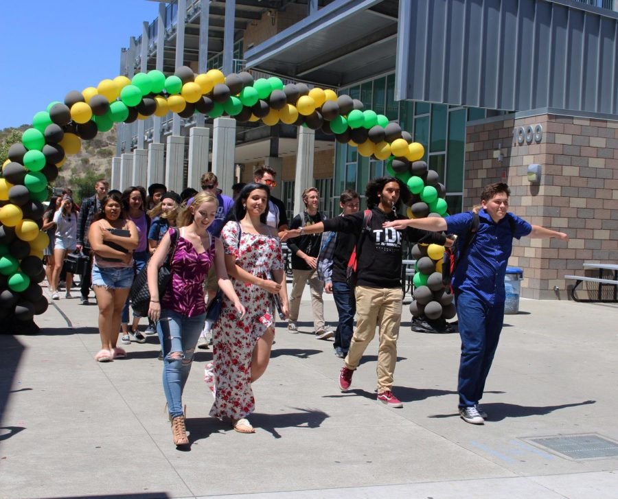 Erin Paulin and Mia Bodnar stand left of Jacob Nipper and Darius Rhamanian while beginning their departure from the Sage Creek campus at the senior walk off.