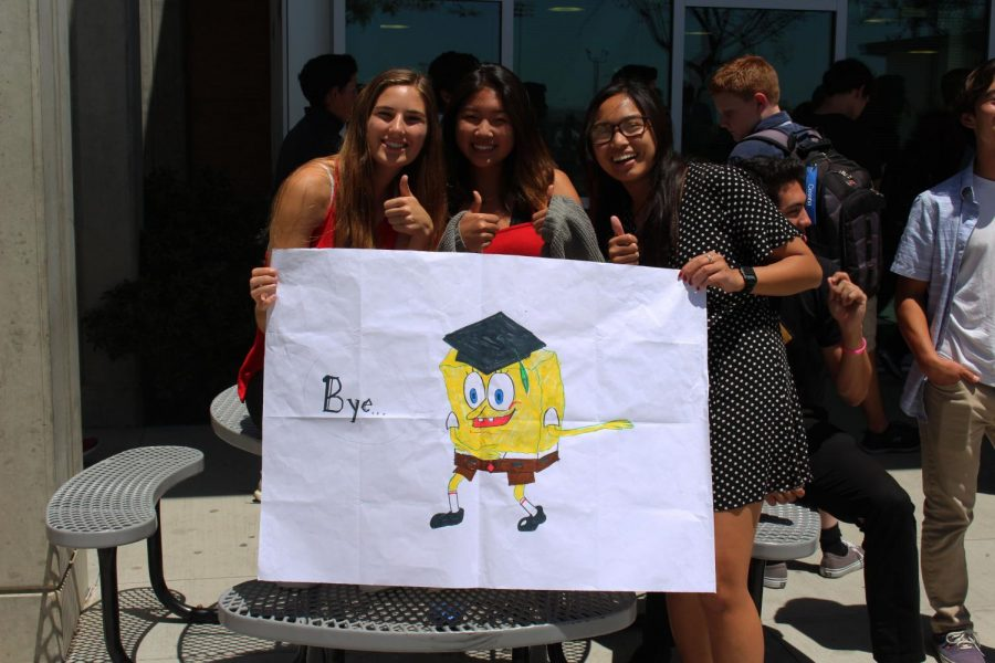 Juniors Summer Fitzgerald (left), Meghan Kim (center), and Kaelin Zablan (right) display a poster created by Zablan as a send off to the graduating class.