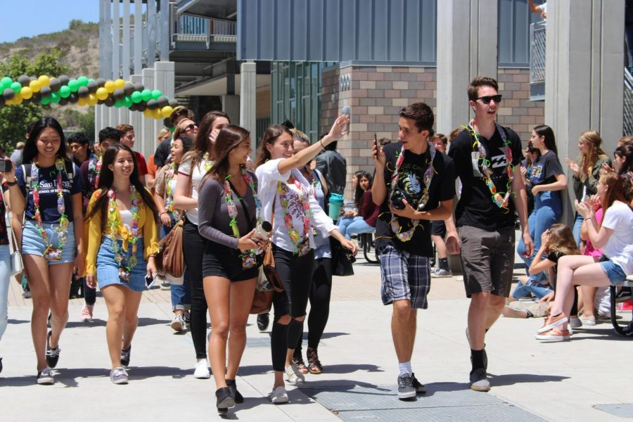 Students in Mrs. Andersson's advisory class are applauded as they leave depart from the Sage Creek campus during the senior walk off.