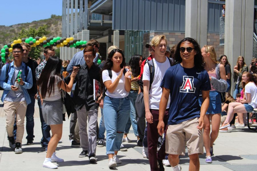Nick Miyamoto leads the remainder of his advisory class towards the front gates of the school during their senior send off.