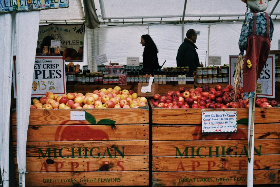 Michigan apples sit in crates ready to be sold at this farmers market. Farmers markets provide fresh produce to their customers in a way that supports local business and the health of our environment.