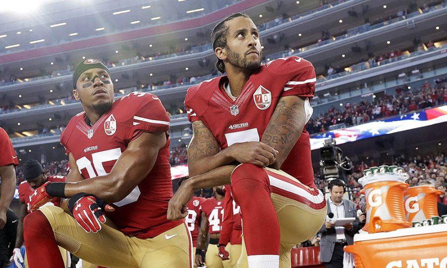 Former+49ers+quarterback+Colin+Kaepernick+kneels+during+the+national+anthem+before+a+game.+This+action+has+sparked+heavy+controversy%2C+prompting+the+changes+made+to+the+NFL%E2%80%99s+employee%E2%80%99s+agreement.