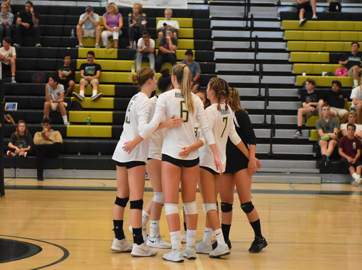 The+girls+varsity+volleyball+team+huddles+in+the+middle+of+the+court+to+show+their+mutual+support+to+one+another+during+their+game+against+Helix+Charter+High+School.+Their+next+home+game+will+take+place+on+Wednesday%2C+Sept.+twelfth%2C+against+Mission+Hills+High+School.
