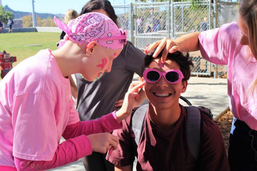 Sophomore Charissa Feldmann paints fellow sophomore Erik Larsen's face for the Pink-out spirit day.
