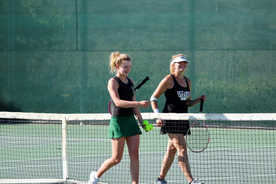 Sophomore Jackie Tucker walks alongside her opponent from Oceanside High School. After a tough match, Sage Creek's girls tennis team ultimately took the victory.