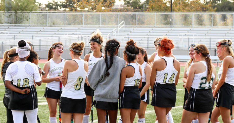 Members of Sage Creek's girls field hockey team smile as their coach gives a motivational pep talk. During the first half of the game, the girls received fierce competition from Rancho Buena Vista High School.