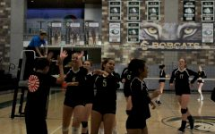 The volleyball team high-fiving one of their fans before the game started. They were gearing up for a tough competition in Patrick Henry.