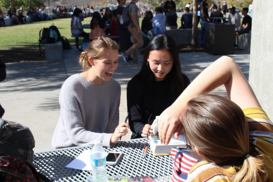 Seniors Tess Tran and Julia Hamilton utilize their lunch period to study for finals and get last minute help from their friends. This has been a common custom for Sage Creek students as they prepare to do their B.E.S.T.