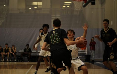 Sage Creek varsity basketball team takes the offense against the Knights with Brady Canfield leading the charge. Even though San Marcos set up a defender, Canfield pressured through to open themselves up for the basket.
