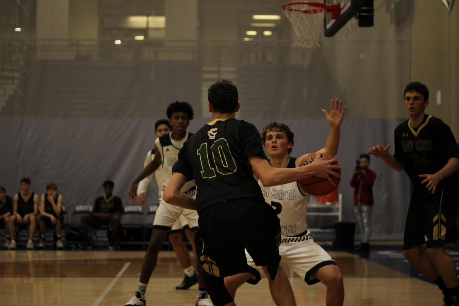 Sage+Creek+varsity+basketball+team+takes+the+offense+against+the+Knights+with+Brady+Canfield+leading+the+charge.+Even+though+San+Marcos+set+up+a+defender%2C+Canfield+pressured+through+to+open+themselves+up+for+the+basket.+