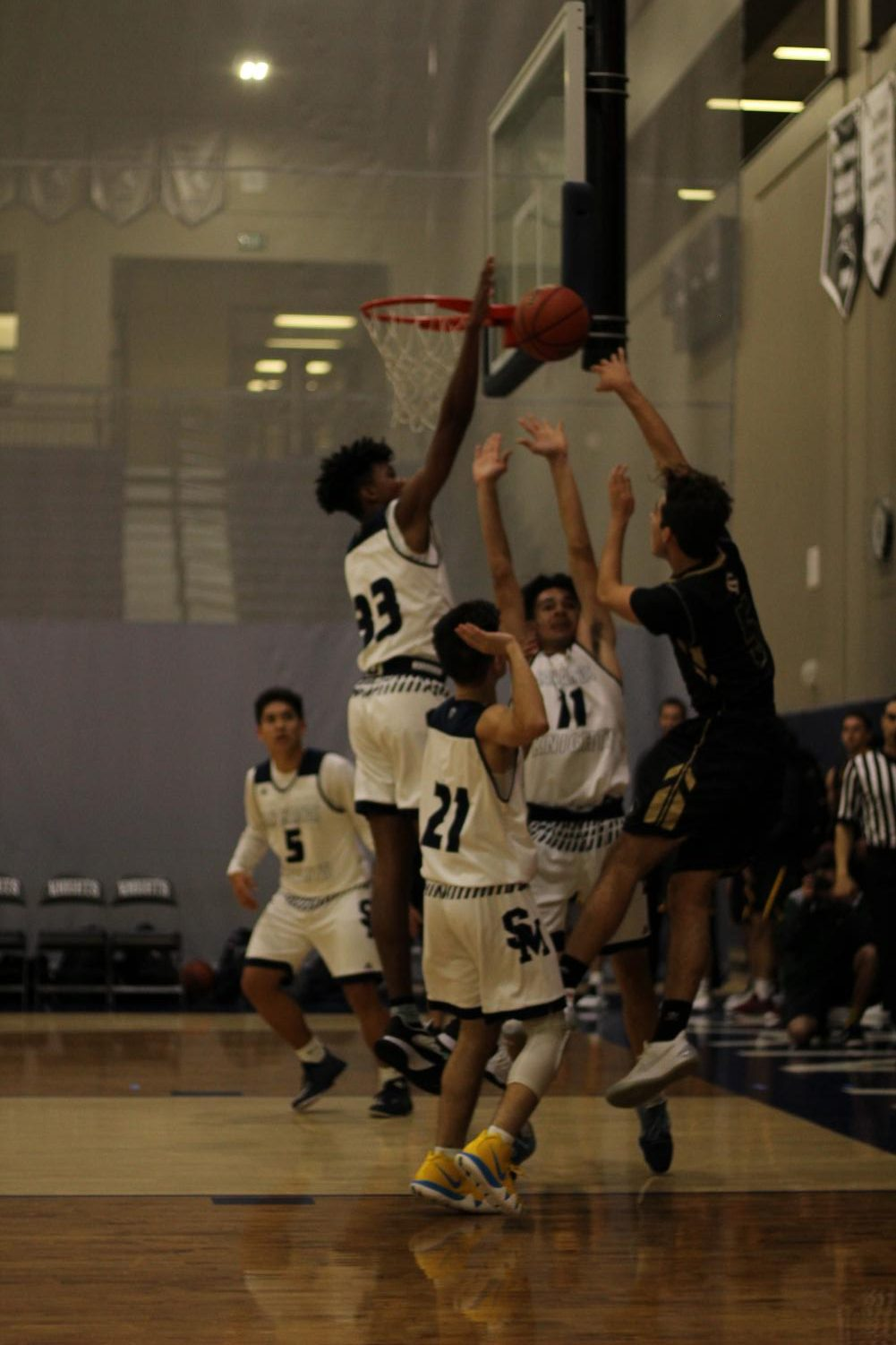 As+a+Sage+Creek+varsity+player+jumps+up+to+shoot+the+ball%2C+he+is+met+with+an+attempted+block+by+the+San+Marcos+team.+