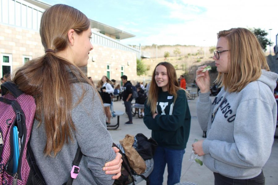 Sophomore Eleni Mowry talks with her eighth grade sister Lauren Mowry at lunch. Several eighth grade students shadowed their older siblings.
