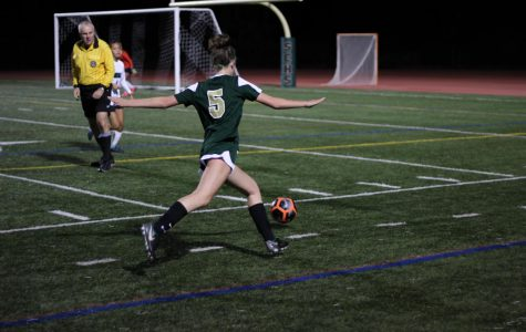 As she kicks the ball up the side line, Mary Grace Feldman avoids the defending players. When she reaches the corner of the field, Feldman kicks the ball towards the goal where her teammates are ready to make a shot.