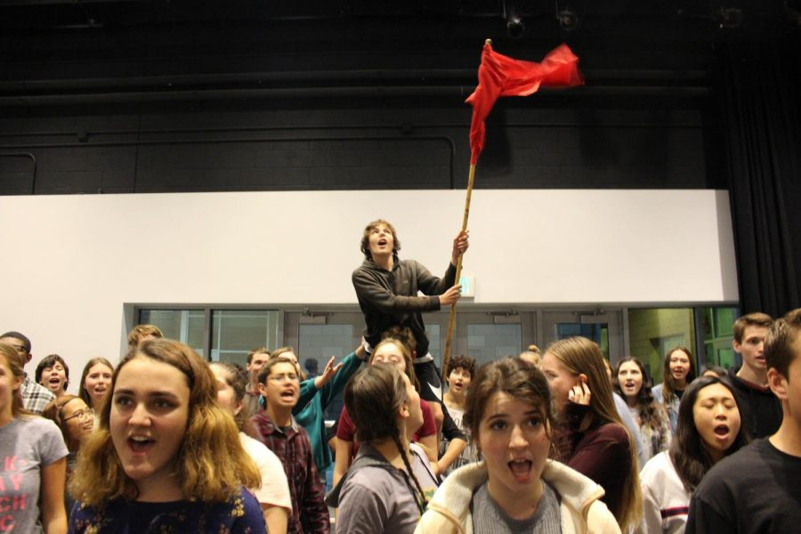 The cast of Les Miserables sing their hearts out in rehearsal, waving a flag of revolution above their heads. The students worked hard over the last month, and continue to practice their show until February.