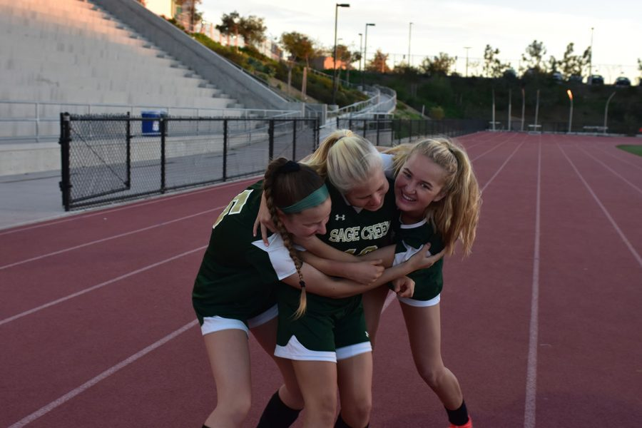 Varsity soccer players Mary Feldmann and Cierra Healy embrace Kat Sumwalt in a hug before preparing for their game last Tuesday, Nov. 27. The varsity team warmed up for their under the lights game while the junior varsity game was still taking place.