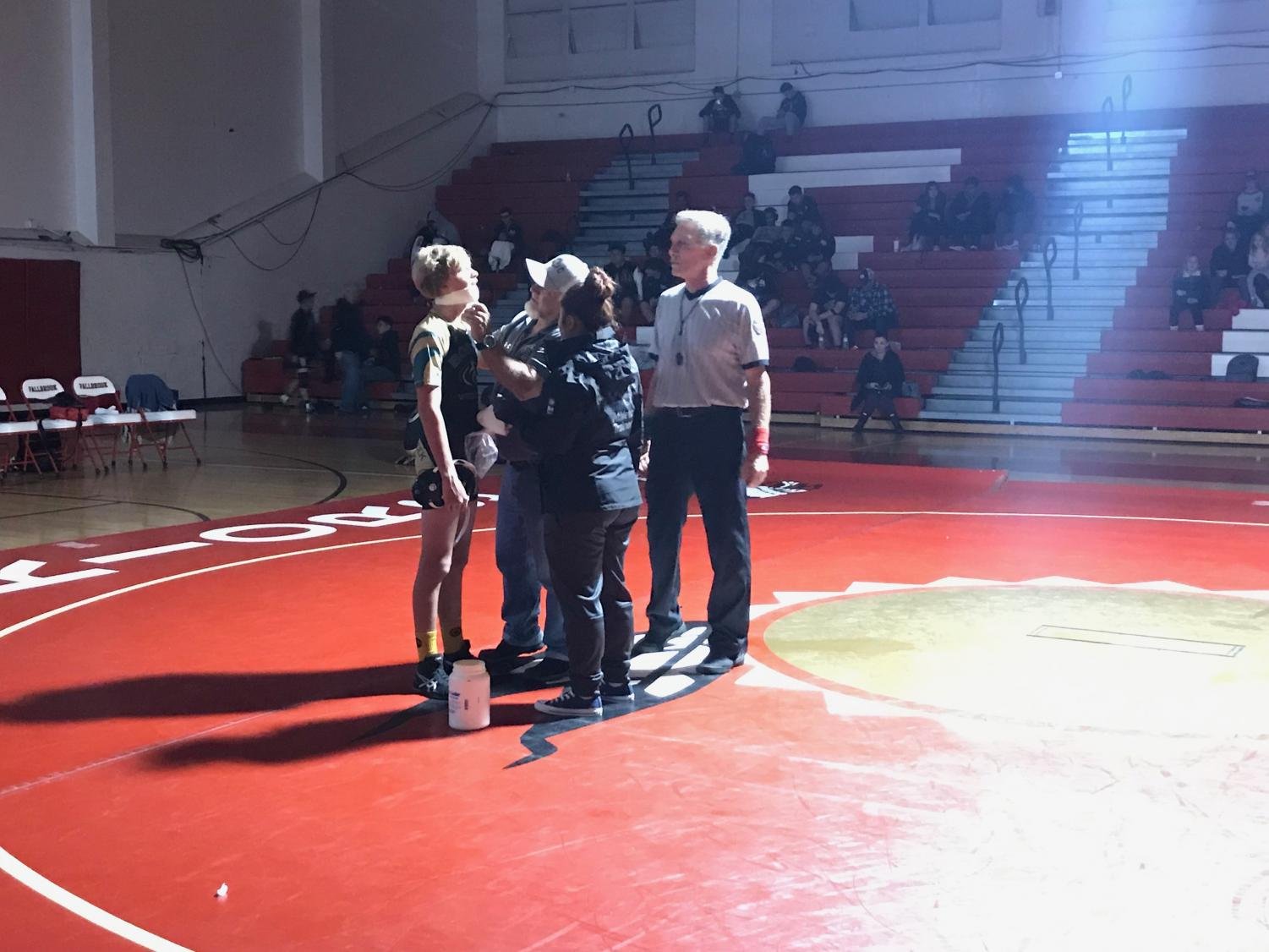 Freshman+wrestler+Peter+Rubin+gets+his+lip+taped+by+Coach+Brian+Kirby+as+the+referee+and+Fallbrook+athletic+trainer+watch.+On+Thursday%2C+Dec.+6%2C+wrestling+had+a+tri-duel+against+Fallbrook+and+Army+Navy+in+which+Rubin+busted+his+lip.+After+the+referee+stopped+the+match+two+times+due+to+the+blood%2C+Kirby+decided+to+tape+Rubin%E2%80%99s+mouth+closed+in+order+to+stop+the+blood.+Rubin+won+both+matches+with+a+pin.