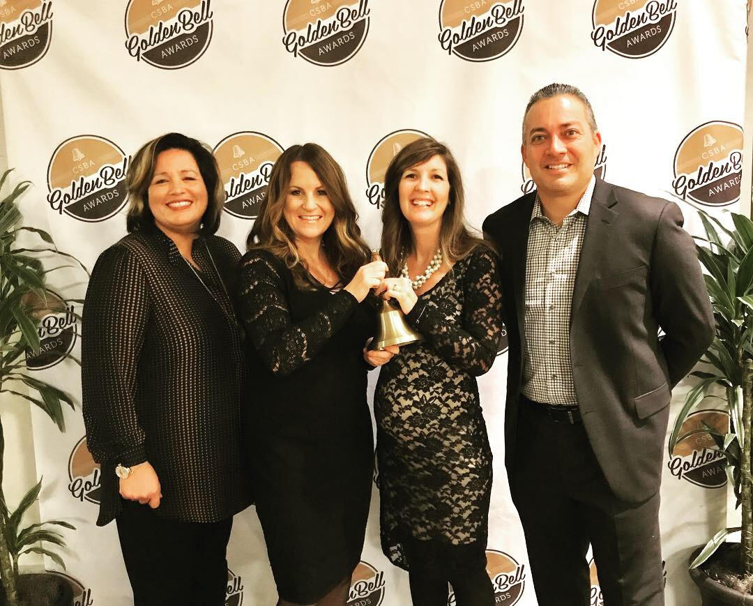 Standing left to right is Claudine Jones, from CUSD Board of Trustees; Shannon Alberts, Sage Creek English teacher; Corrie Myers, Sage Creek English Teacher; and César Morales, Sage Creek Principal. They are holding the Golden Bell Award which the Genius Project was recognized for through the CSBA.