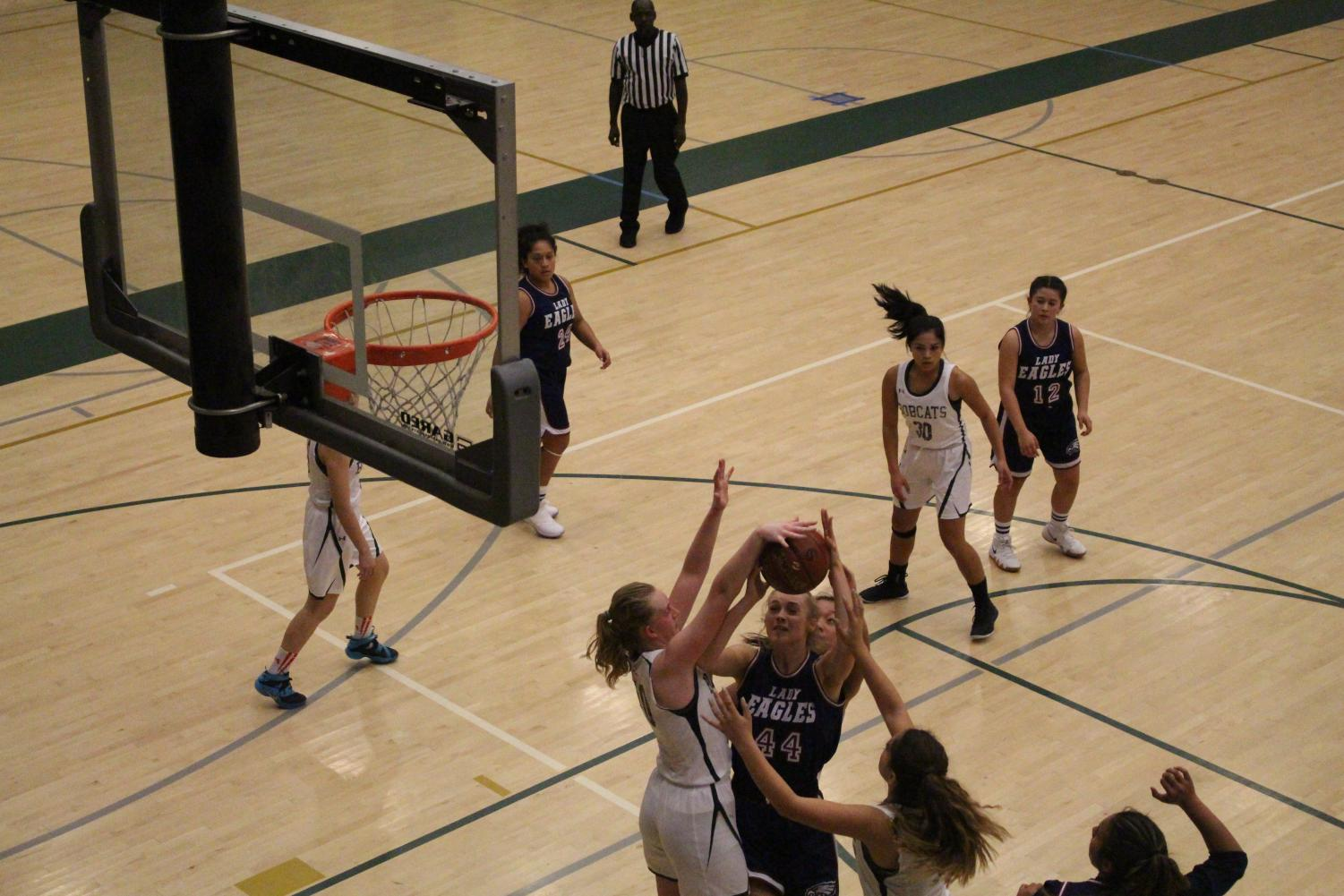 Junior Claire Perhach blocks an opposing player as she goes up for a layup. Perhach is a vital part of the defense providing a strong presence down low.