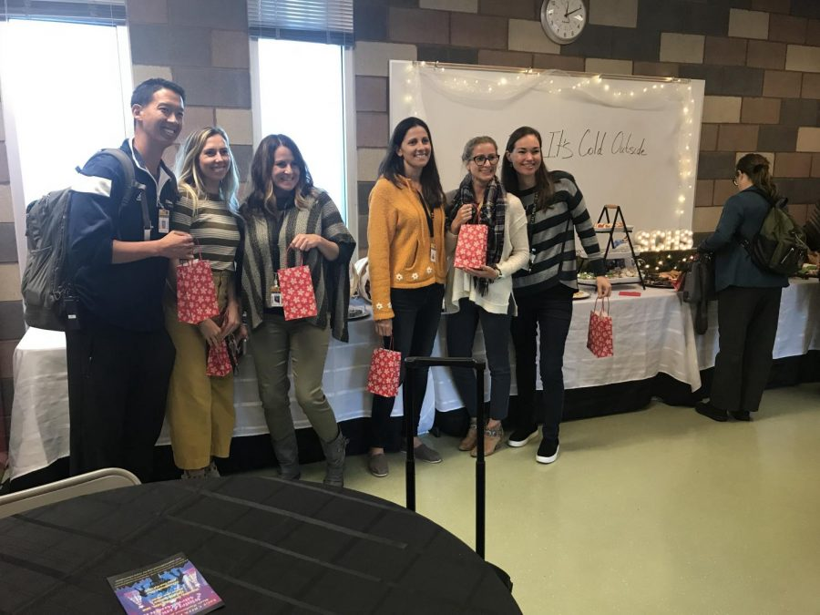 Some of Sage Creek's teachers and staff pose on Wednesday, Dec. 12, with their treat-filled bags. PTSA collected various sweets through the week to show the teachers and staff how appreciated they are during the holiday season.