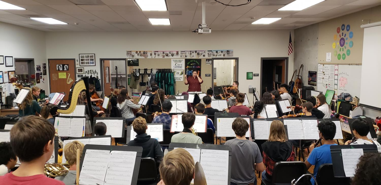 Juliana Quinones in the midst of conducting her orchestra class. They are preparing for upcoming performances.
