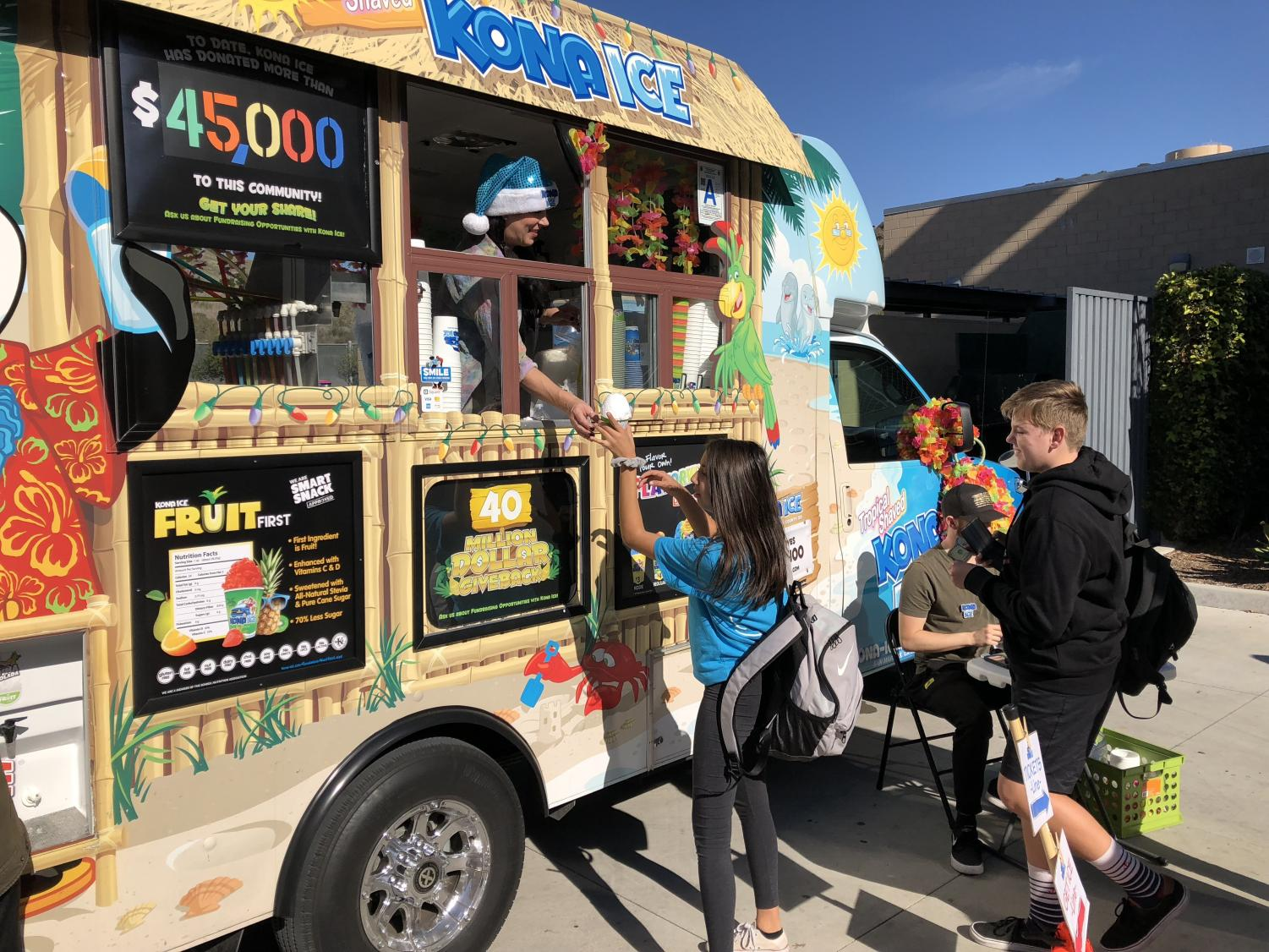 Students+gather+at+the+Kona+Ice+truck+to+collect+their+frozen+treats.+Students+who+brought+in+three+or+more+cans+for+the+canned+food+drive+fundraiser+received+a+discounted+Kona+Ice+treat+and+the+winning+class+received+free+Kona.