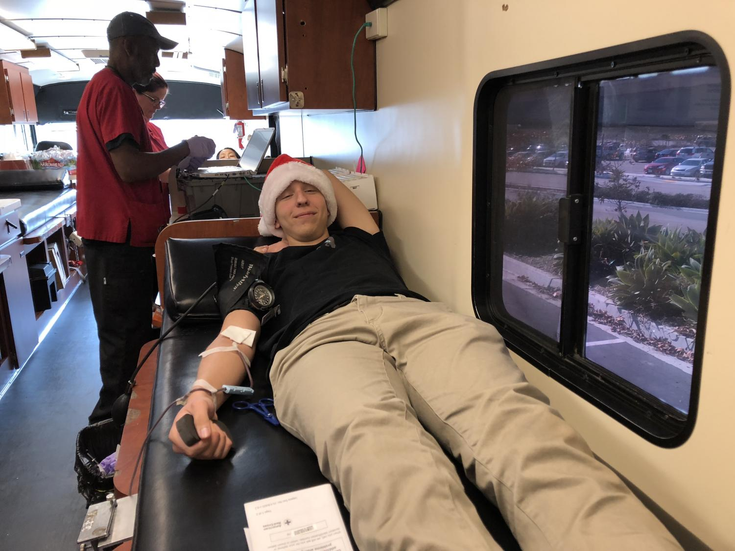Senior+Nick+Rhead+gives+blood+inside+the+American+Red+Cross+blood+donation+bus+on+Wednesday.+The+Red+Cross+provides+about+40+percent+of+America%E2%80%99s+blood+all+of+which+is+gathered+from+volunteers+from+around+the+country.