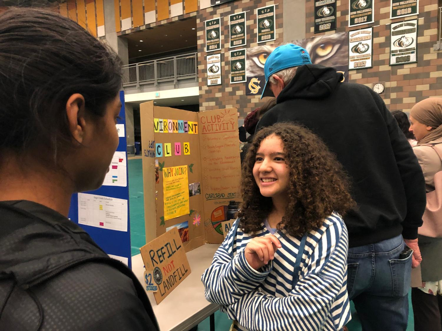 An+incoming+eighth-grader+asks+junior+Lavanya+Pandey+about+Science+Olympiad.+Many+clubs%2C+sports+and+classes+were+on+display+at+this+year%E2%80%99s+Eighth+Grade+Showcase+Tuesday+evening%2C+especially+ones+that+could+be+pivotal+in+the+eighth+graders%E2%80%99+decisions+on+which+of+the+high+schools+would+be+the+best+fit.+